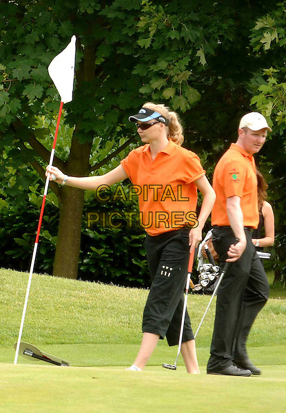 JODIE KIDD .competes in the Mini Masters Charity Golf Event - a par-3 celebrity golf tournament in aid of LEUKA. The match will raise money for research into and treatment of Leukaemia..Duke's Meadow Golf Club, London, England, UK, July 14, 2008..full length sport playing golfing orange top shirt visor black cropped trousers club flag pole .CAP/WIZ.©WizardCapital Pictures