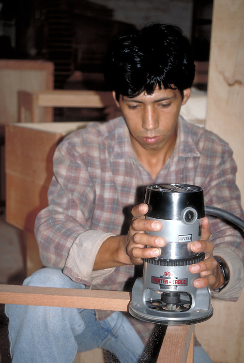 Peruvian furniture craftsman using a router in Lima, Peru