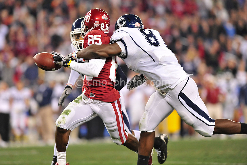 Jan 1, 2011; Glendale, AZ, USA; Oklahoma Sooners wide receiver Ryan Broyles (85) has the ball knocked out of his hands by Connecticut Huskies linebacker Lawrence Wilson (8) after a 64-yard punt return in the 3rd quarter of the 2011 Fiesta Bowl at University of Phoenix Stadium.  The Sooners won the game 48-20.