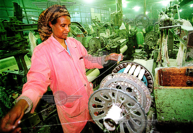 Eritrea, Asmara, 25.12.2000.Worker operating a spinning machine in the Asmara Textile Factory..©Stefan Boness/Panos Pictures