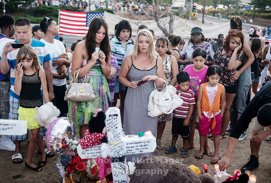 People mourn for the 12 victims of the mass shooting at a shrine built near the Aurora Century 16 movie theater in Aurora, Colorado, Sunday, July 22, 2012. Suspect James Holmes, allegedly went on a shooting spree and killed 12 people and injured 59 during an early morning screening of 'The Dark Knight Rises.'..Photo by MATT NAGER