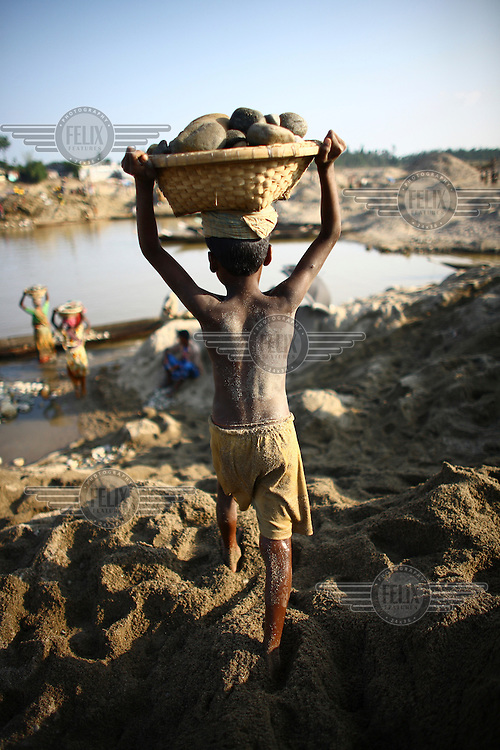 A child carries a basket of stones on his head. At least 10,000 people, including 2,500 women and over 1,000 children, are engaged in stone and sand collection from the Bhollar Ghat on the banks of the Piyain river. Building materials such as stone and sand, and the cement which is made from it, are in short supply in Bangladesh, and commands a high price from building contractors. The average income is around 150 taka (less than 2 USD) a day.