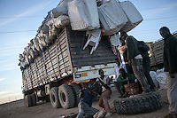 November 22, 2014 - Murzuq region, Libya: A truck loaded with camel skin heading to Niger stops at a black market place as immigrants repair a wheel in the middle of the desert in Southwest Libya. Libya's borders remain largely ungoverned, and securing the periphery is among the country's greatest challenges. Weak border control allows markets in arms, people, and narcotics to thrive alongside everyday trafficking in fuel and goods, with profound consequences for the region as a whole. (Photo/Narciso Contreras)