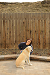 Matisse Weigle in bare backyard with her dog.
