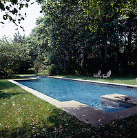 A large swimming pool takes advantage of the shelter provided by the garden's mature trees