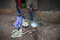 Uganda, Angi. Nabiirah SserKumba (29) and her husband Hakim have seven children. She uses the BioLite stove as it's faster and emits less smoke. It also charges a light, portable radio and her mobile phone. Cooking with her son Jawaduh (5).