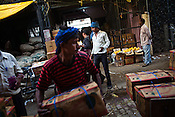 Workers load and unload crates of mango at the whole sale fruits and vegetable market in Azadpur Mandi in Old Delhi, India. Photo: Sanjit Das/Panos for Time