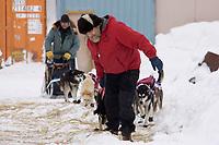 Volunteer checker Jasper Bond helps park Rick Swenson's team in Elim on Tuesday during Iditarod 2008
