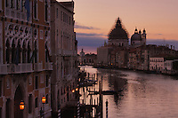 Early morning on the Grand Canal in Venice, Italy.Showing San Maria della Salute with dome covered in scaffolding.