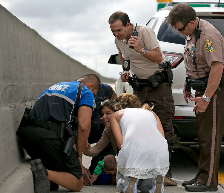 Rescuers with Pamela Rauseo, 37, at center, who performed CPR on her nephew, five-month-old Sebastian de la Cruz, after pulling her SUV over on the side of the road along the west bound lane on Florida state road 836 just east of 57th Avenue around 2:30pm on Thursday, February 20, 2014.  At right is Lucila Godoy who stopped her car to assist in the rescue. At left is Sweetwater officer Amauris Bastidas who was passing by and stopped to the aide the baby.