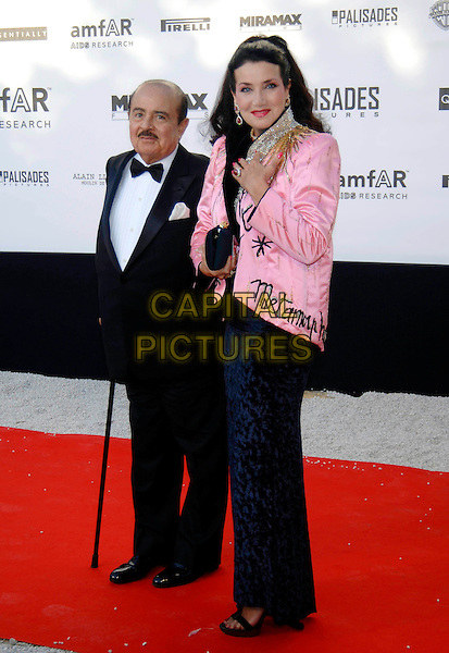 ADNAN KHASHOGGI & GUEST.58th Cannes International Film Festival: Cinema Against AIDS 2005 in aid of amfAR.May 19th, 2005.full length  black tuxedo cane pink silk satin jacket chopard blue skirt.www.capitalpictures.com.sales@capitalpictures.com.©Capital Pictures