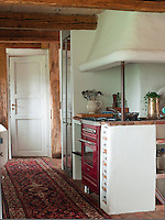 This country-style kitchen is equipped with modern kitchen appliances, such as the red cooker and floor-to-ceiling refrigerator