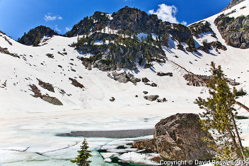 Snow and ice still cling to high mountains in early summer at Grand Teton National Park.