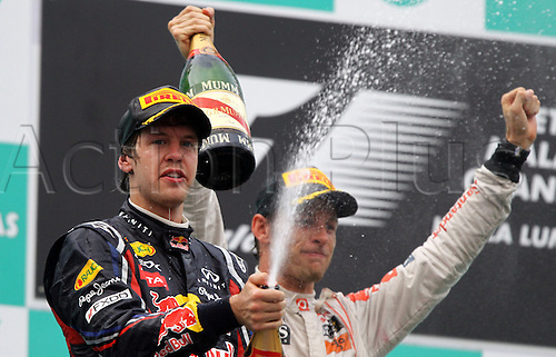 German Formula One driver Sebastian Vettel (L)of Red Bull Racing celebrates with British Formula One driver Jenson Button of McLaren Mercedes after winning the Formula One Grand Prix of Malaysia at the Sepang circuit, outside Kuala Lumpur, Malaysia, 10 April 2011.