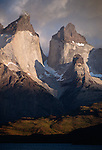 Early morning light bathes the monolith of Cuernos del Diablo in gold light, Torres del Paine National Park, Chile.