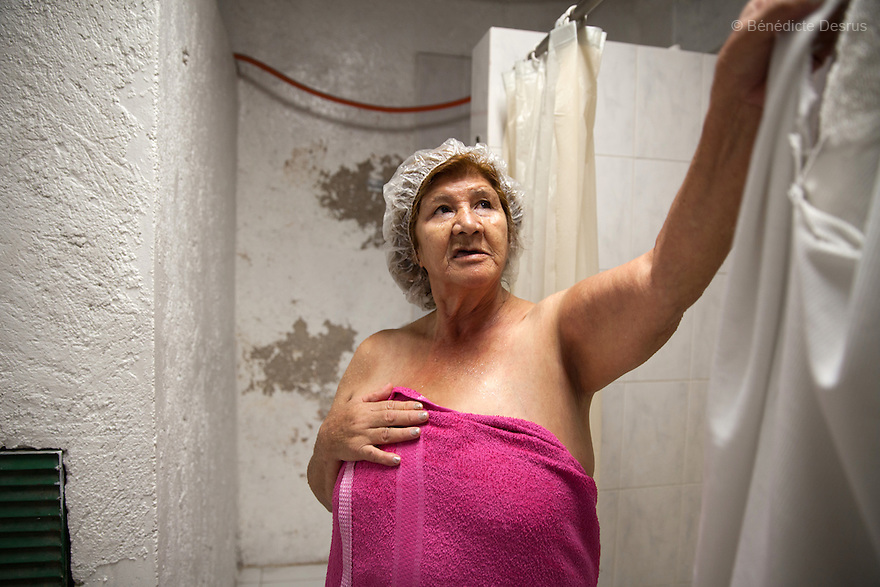 Gloria, a resident of Casa Xochiquetzal, takes a shower at the shelter in Mexico City, Mexico on September 3, 2013. Casa Xochiquetzal is a shelter for elderly sex workers in Mexico City. It gives the women refuge, food, health services, a space to learn about their human rights and courses to help them rediscover their self-confidence and deal with traumatic aspects of their lives. Casa Xochiquetzal provides a space to age with dignity for a group of vulnerable women who are often invisible to society at large. It is the only such shelter existing in Latin America. Photo by Bénédicte Desrus