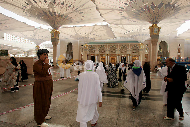 Muslim pilgrims walk outside the Prophet Mohammed Mosque in the Saudi holy city of Medina on November 2, 2010. More than three million Muslims are expected to converge on the holy cities of Mecca and Medina in western Saudi Arabia for the hajj. Islam's Prophet Mohammed is buried in Medina's landmark mosque, which is Islam's second holiest shrine after Mecca. Photo by Mahfouz Abu Turk