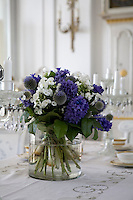 A large vase of hyacinths and globe thistles on the dining room table