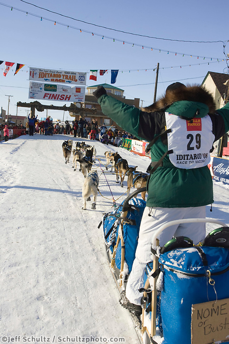 Rookie musher Laura Daugereau reaches the burl arch finish line with her *Nome or Bust* sign on the back of her sled on Saturday afternoon.