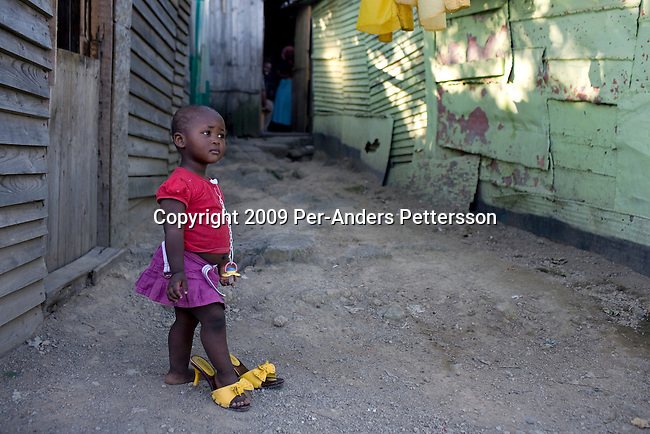 EAST LONDON, SOUTH AFRICA - MARCH 10: A young girl plays with her mothers shoes outside the family home on March 10, 2009, in Duncan Village a poor township outside East London, South Africa. This area is one of the most popular ANC areas and many of its leaders grew up in the Eastern Cape province. Many people are disappointed in the ruling party and after 15 years of power, people?s lives have not changed much to the better. In Duncan Village, there?s lack of service delivery such as housing, electricity, and running water. Garbage is left on the streets and the municipality is only collecting it once a week, or they often skip a week. About 23 million South Africans are registered to vote on the April 22 national election. Jacob Zuma will most likely be the third elected head of a democratic South Africa. (Photo by: Per-Anders Pettersson/Getty Images)....