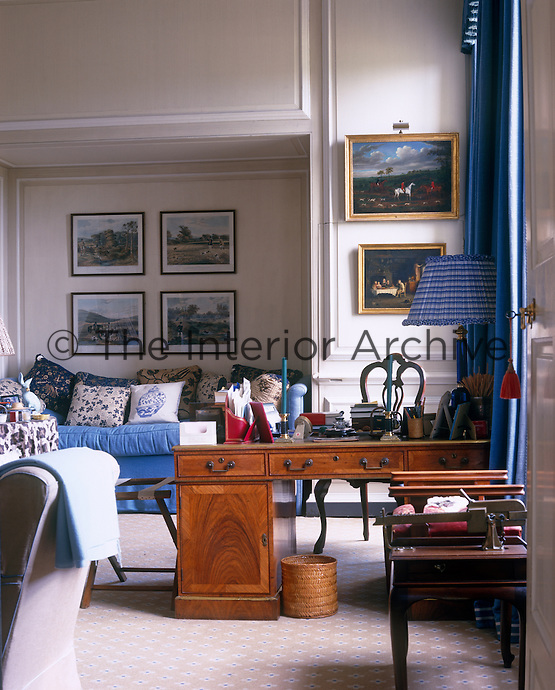 The comfortable study/sitting room is decorated with paintings and prints of hunting scenes