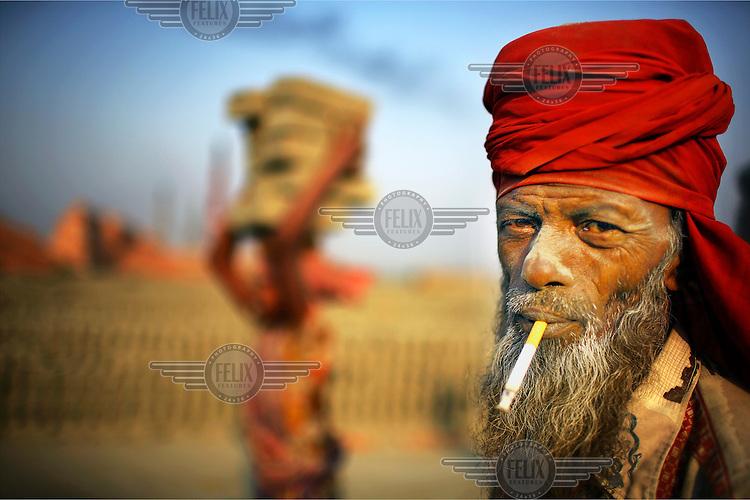 A labourer at a brick factory smoking a cigarette.