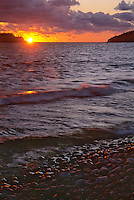 The sun sets into Lake Superior, from the shores of Gargantua Bay in Ontario, Canada's Lake Superior Provincial Park on the eastern end of Lake Superior