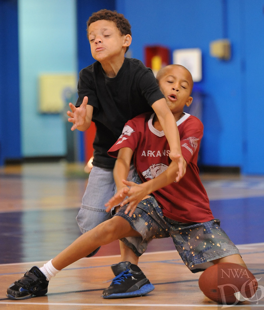 NWA Media/ANDY SHUPE - Campers Bryson Jackson, 7, left, and Dante Adams, 7, reach to catch a football while enjoying a game of 7-on-7 football prior to leaving on a field trip to the Wilson Park Pool Wednesday, July 9, 2014 at the Yvonne Richardson Community Center in Fayetteville. The students are participating in the Summer Fun4Kids Camp, a summer camp being held at the center through Aug. 2.