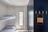 A child's bedroom boasts a set of contemporary bunk beds and a robust built-in cupboard
