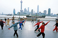 "China. Shanghai. Downtown. City center. Pudong skyline seen from ""The Bund"". Early morning a group of chinese  women are doing their daily exercices. They dance with swords and knifes. Over 1 and 1/2 times larger than urban Shanghai itself, the Pudong new area consists of the entire eastern bank of the Huangpu river. Pudong is the new area of development where the growing business needs constantly new modern high buildings, real ""skyscrapers"". Pudong has become Shanghai and China's economic powerhouse.The Bund is the most impressive 2 km in Shanghai. © 2002 Didier Ruef"