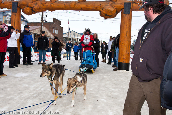 Wattie McDonald and wife ride the sled out of the Nome finish chute to the dog yard during the 2010 Iditarod