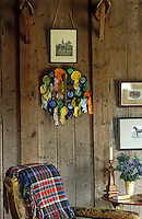 A collection of rosettes and black and white photographs of horses is displayed on the rough wooden wall of the bothy