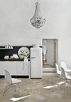 The kitchen features a free-standing fridge and contemporary black and white units, contrasting with the stone-tiled floor