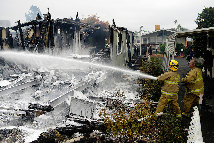 Napa County volunteer firefighters Mike Morisoli, left, and Steve Jones spray a mixture of water and foam on the remnants of a mobile home that caught fire and burned down after a magnitude 6.0 earthquake struck in the early morning of August 24, 2014,  in Napa, California.