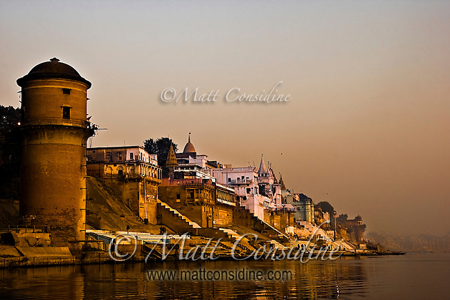 Dawn light filtered through smoke and mist gradually illuminates the ancient spires on the banks of the Ganges.<br /> (Photo by Matt Considine - Images of Asia Collection)
