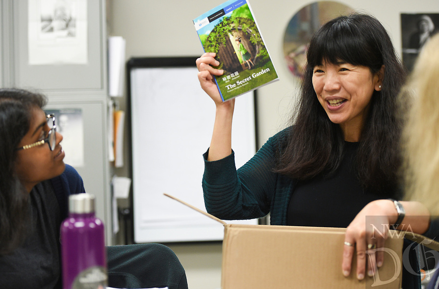 """NWA Democrat-Gazette/CHARLIE KAIJO Mandarin teacher Lin Chen (right) holds up a reader as Immaculin Joe, 17, of Bentonville (left) looks on, Friday, August 9, 2019 at Haas Hall Academy in Bentonville.<br /> <br /> """"There's more pathways for you,"""" said Victor Gao, explaining why he chose Mandarin to study. """"You can choose more careers especially if you want to be a doctor or get in to business."""""""