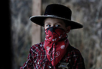Bandit/cowbow/sheriff, Tanner Lauman hides behind his red bandanna.<br /> <br /> Kitty Lauman trains mustangs--as she says working with the horses, not against them.  They have a ranch in Prineville, OR.<br /> <br /> Kitty, her husband Rick and their children, Josie, 2 &frac12;,  and Tanner, 5,  ride mustangs. Kitty Lauman started her career as a horse trainer at the tender age of nine, under the guidance of her grandfather, John Sharp. <br /> <br /> She later became a top Pee Wee and High School Rodeo contestant, competing in barrel racing and cutting, among other events. Despite her mother's assertion that &quot;horse training isn't a real job,&quot; Kitty managed to make a living as a trainer after high school (and her mom now helps out with the business!) <br /> <br /> Kitty won the title of Miss Rodeo Oregon in 1994, and since then, has continued to expand her horse training knowledge and experience.  She placed second in the Extreme Mustang Makeover, a national competition in 2008.