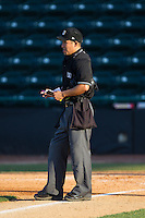 Home plate umpire Takahito Matsuda updates his lineup card during the South Atlantic League game between the Augusta GreenJackets and the Hickory Crawdads at L.P. Frans Stadium on May 11, 2014 in Hickory, North Carolina.  The GreenJackets defeated the Crawdads 9-4.  (Brian Westerholt/Four Seam Images)