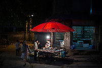 A woman sells chicken and duck pieces at a street stall at the bottom of Shibati, or 18 Steps, in central Chongqing, China.