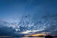Alaska Airlines jet departs Sitka airport, Mount Edegcumbe at sunset, Sitka sound, southeast, Alaska.