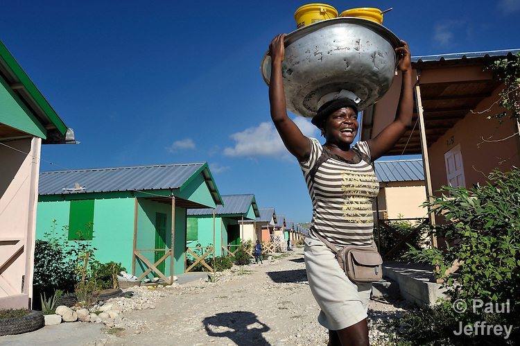 Metelus Jonotas shouts her offers to prospective customers as she sells beans and rice and other basic foodstuffs from a pan that she carries on her head as she walks through the Corail camp for resettled earthquake survivors north of quake-ravaged Port-au-Prince, where she lived before coming to Corail several months after the 2010 quake. She has three children, two of whom go to schools in the camp built by the United Methodist Committee on Relief (UMCOR).
