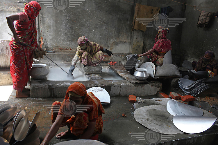 Women working in a silver cooking pot factory in Old Dhaka. They work 10 hour days in hazardous conditions, for a weekly wage of 600 taka (8.6 USD)...