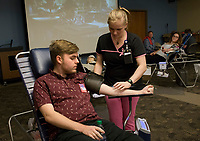 NWA Democrat-Gazette/CHARLIE KAIJO Phlebotomist Kristen Walker draws blood from Isaac Gastineau of Rogers on Thursday, October 12, 2017 at Northwest Arkansas Community College in Bentonville. The Community Blood Center of the Ozarks took donations at the college's student union.