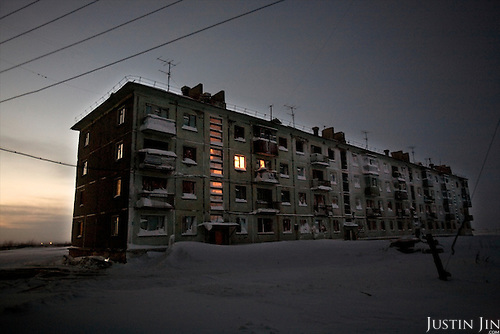 Buildings around Vorkuta are being surrendered to the elements as people flee to the south. In this apartment block on the edge of the tundra in Yor Shor village outside Vorkuta town, only one family is left..Vorkuta is a coal mining and former Gulag town 1,200 miles north east of Moscow, beyond the Arctic Circle, where temperatures in winter drop to -50C. .Here, whole villages are being slowly deserted and reclaimed by snow, while the financial crisis is squeezing coal mining companies that already struggle to find workers..Moscow says its Far North is a strategic region, targeting huge investment to exploit its oil and gas resources. But there is a paradox: the Far North is actually dying. Every year thousands of people from towns and cities in the Russian Arctic are fleeing south. The system of subsidies that propped up Siberia and the Arctic in the Soviet times has crumbled. Now there's no advantage to living in the Far North - salaries are no higher than in central Russia and prices for goods are highe