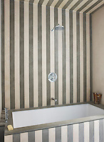 The walls of the guest bathroom are clad in stripes of limestone