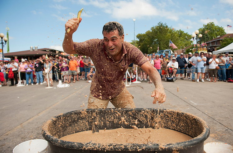 "UNITED STATES - AUGUST 16:  A contestant competes in an ""outhouse race"" at the Iowa State Fair in Des Moines, Iowa.  One leg of the event is to retrieve a corn cob from a tub of pig feed.  (Photo By Tom Williams/Roll Call)"