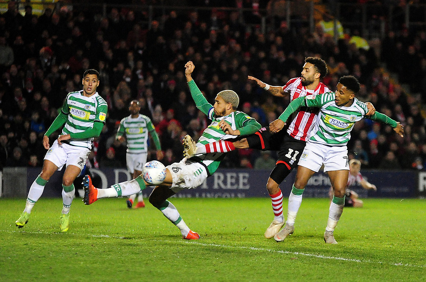 Lincoln City's Bruno Andrade is denied by Yeovil Town's Omar Sowunmi, left, and Rhys Browne<br /> <br /> Photographer Andrew Vaughan/CameraSport<br /> <br /> The EFL Sky Bet League Two - Lincoln City v Yeovil Town - Friday 8th March 2019 - Sincil Bank - Lincoln<br /> <br /> World Copyright © 2019 CameraSport. All rights reserved. 43 Linden Ave. Countesthorpe. Leicester. England. LE8 5PG - Tel: +44 (0) 116 277 4147 - admin@camerasport.com - www.camerasport.com