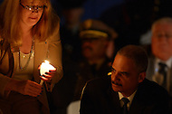 May 13, 2013  (Washington, DC) Madeline Neumann, National President of the Concerns of Police Survivors and U.S. Attorney Eric Holder, light candles candles in tribute to fallen officers during the 25th Annual Candlelight Vigil hold candles at the National Law Enforcement Officers Memorial. (Photo by Don Baxter/Media Images International)