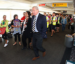 Walter Smith walks past holidaymakers waiting to board their flight as Rangers head out to Stuttgart