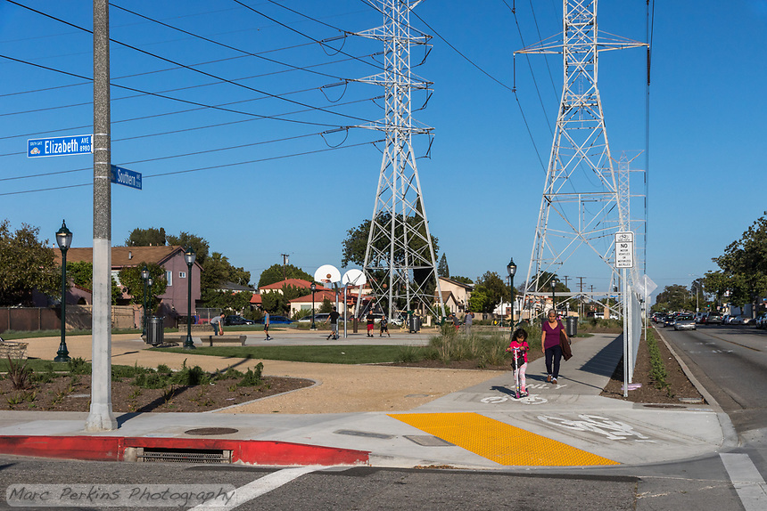 What appears to be a grandmother and her daughter walk along the protected sidewalk of State Street Park in front of youths playing basketball.   Many elements of State Street Park can be seen in this image: a wide paved path for pedestrians that's protected from the busy street, clearly marked bike paths, decomposed granite walking trails, lighting, and recreational areas (in this case: basketball courts with youths playing basketball).  Taken at the corner of Southern and Elizabeth.
